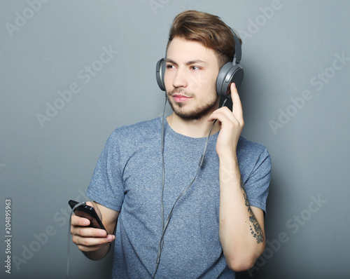 Fotografie, Obraz  Man holding mobile phone and lictening to music over grey background