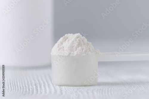 a scoop with white powder closeup and a jar on gray background Fototapeta
