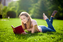 Girl Reading Book Lying On The Lawn