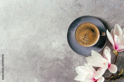 Photo  Blue cup of black espresso coffee and spring flowers magnolia branches over grey texture background