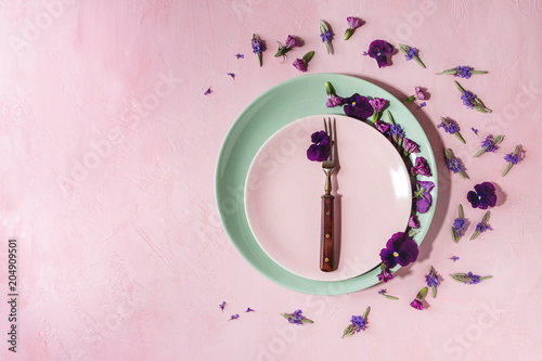 Foto op Canvas Aromatische Variety of purple edible flowers for dish decorating with empty ceramic plate and fork over pink pastel background. Top view, space.