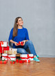 Smiling woman looking up sitting with heap of present gift boxes