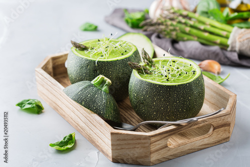Seasonal creamy asparagus spinach soup served in a round zucchini