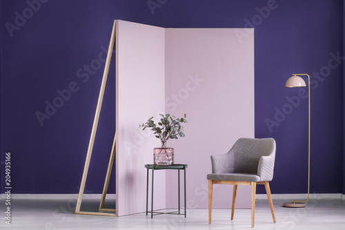 Fotografia  Real photo of twigs in a pink, glass vase on a metal table next to a gray armcha