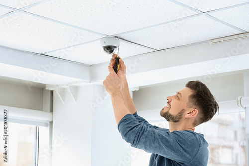 Fotografie, Obraz  Technician installing CCTV camera on ceiling indoors