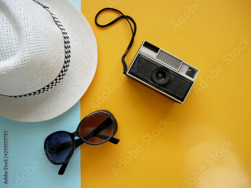 Fototapeta Flat lay of accessories items for travel with camera, hat and sunglasses on colorful background. Holiday concept. obraz na płótnie