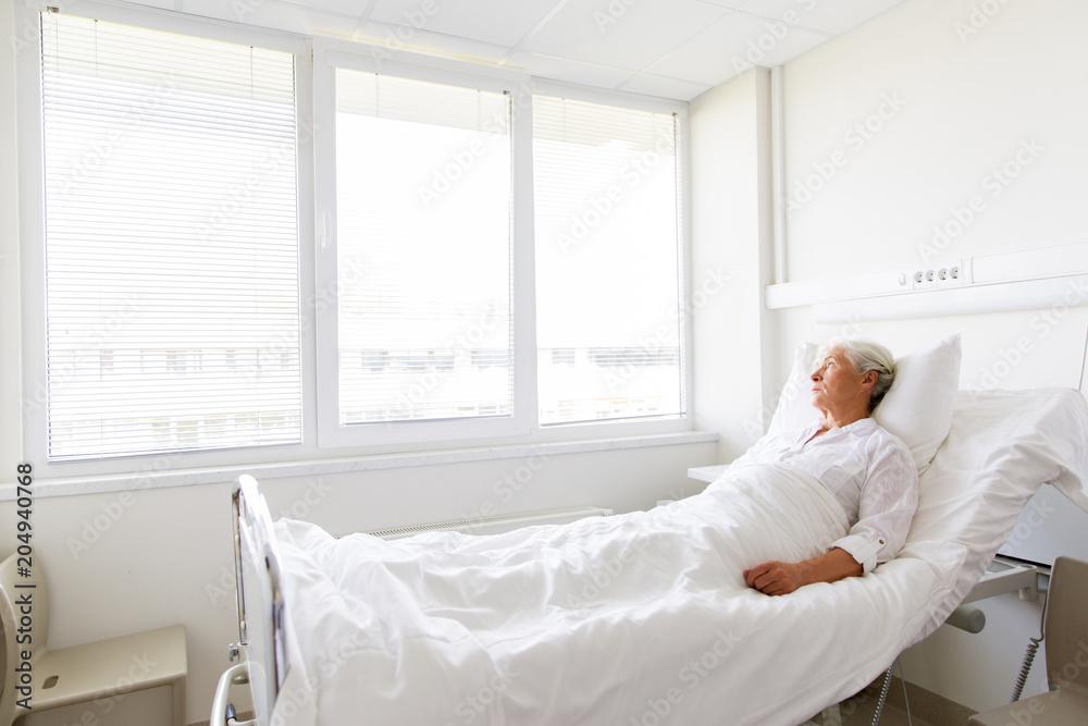 Fototapeta medicine, healthcare and old people concept - sad senior woman lying on bed at hospital ward