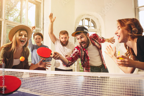 Fotografia  Group of happy young friends playing ping pong table tennis