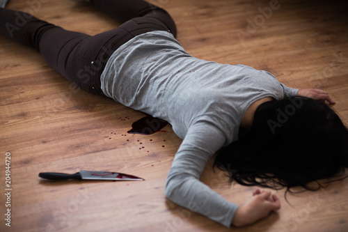 murder, kill and people concept - dead woman body and knife in blood lying on fl Canvas Print