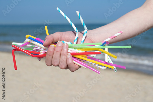 Fotografía  Close Up Of Hand Holding Plastic Straws Polluting Beach