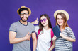 Group of happy smiling students dressed in t-shirts and hats and eyeglasses before purple background