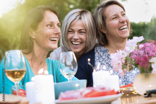 Photographie  three female friends in their 40s share a moment of complicity