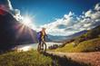 Leinwandbild Motiv woman on e-bike enjoying view to a beautiful lake
