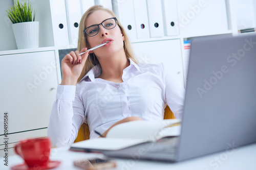 Young Caucasian business woman in glasses looks thoughtfully into the distance holding the pen in her mouth and thinks.