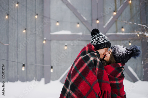 163a9c47318 Cheerful loving couple in warm cozy clothes hugging and warming up with  colorful blanket in the