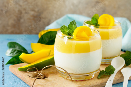 Mango panna cotta with fresh mango and topping with mango jelly on a stone or slate background. Traditional italian dessert. Copy space.