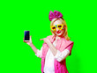 canvas print picture - Cheerful pretty woman in carnival glasses and a pink bow, pointing with her finger to the smartphone screen, isolated on bright colorful background. Looking at the camera