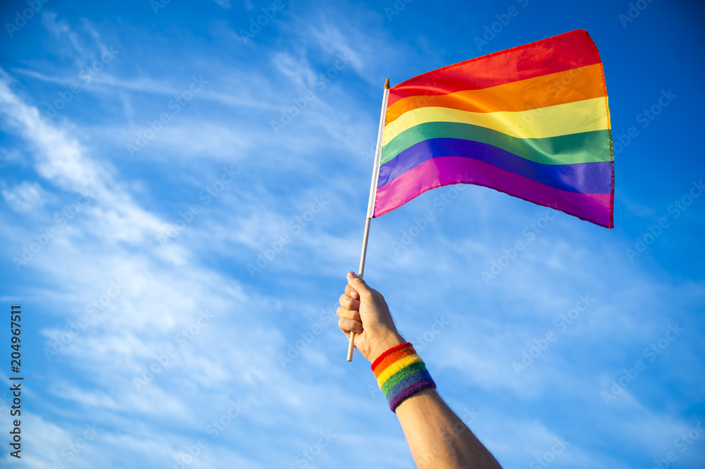 Fototapeta Colorful backlit rainbow gay pride flag being waved in the breeze against a sunset sky.