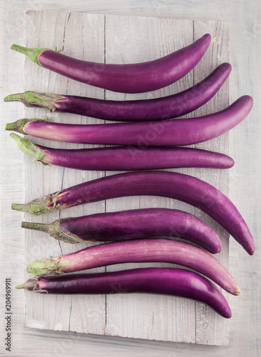 Fresh, beautiful purple violet eggplants decorated on a white wood table, studio shoot can be used as background
