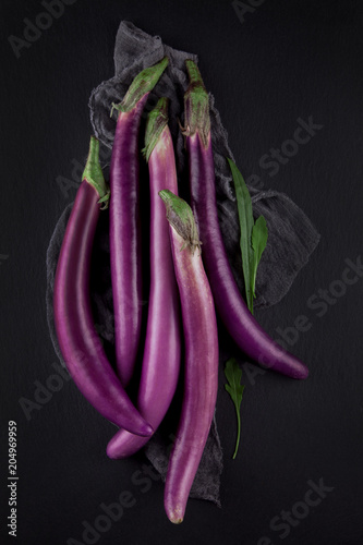 Fresh, beautiful purple violet eggplants decorated on a dark slate table, studio shoot can be used as background