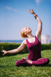 beautiful girl meditates in lotus position sitting on grass on sunny day