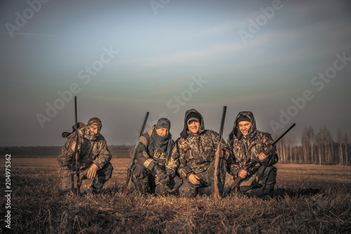 Foto op Canvas Jacht Men hunters group team portrait in rural field posing together against sunrise sky during hunting season. Concept for teamwork friendship and brotherhood.