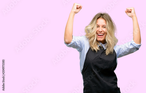 Young shop owner wearing black apron happy and excited celebrating victory expressing big success, power, energy and positive emotions. Celebrates new job joyful