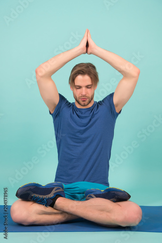 Poster Ontspanning Sportsman relax in lotus pose. Man meditate on yoga mat. Fashion athlete practice yoga in gym. Meditation for body and mind health. Meditation or zen and peace concept