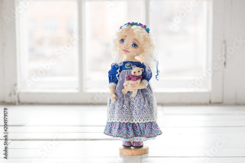 Obraz na plátne Portrait of textile handmade vintage doll with blue eyes, long blond hair in old blue textile dress with gentle print, in white shirt with purple boots on white background