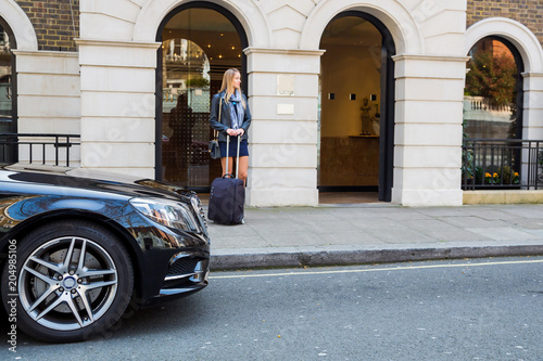 Photo Beautiful girl standing on the street with a suitcase near a fancy car in London