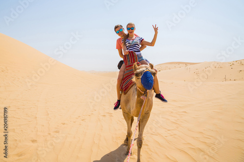 Young couple sitting on a camel in a desert Canvas Print
