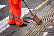 Municipal Worker Sweep The Road With Broomstick And Collects Garbage In  Scoop. Sanitation Worker Sweep Street
