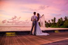 Beautiful Married Couple Standing On A Jetty On Maldives Watching Amazing Purple Blue Sunset. Tropical Wedding.