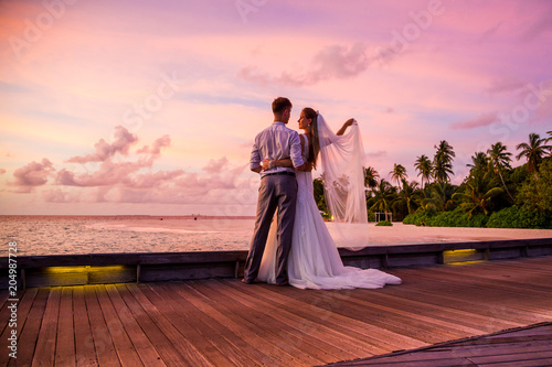 Fototapeta  Beautiful married couple standing on a jetty on Maldives watching amazing purple blue sunset