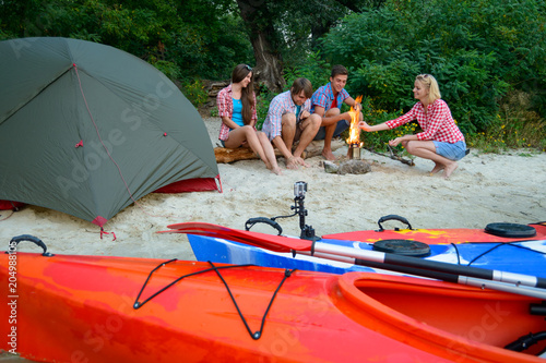 Young Happy Travelers Resting at Evening with Fire on the Sand Beach near Kayaks and Tent.