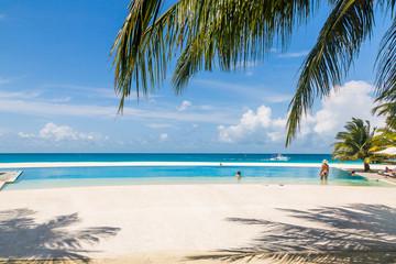 Beautiful golden beach with sunshades on Maldives beach.