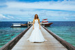 Beautiful bride in a white dress standing on a pier in the Maldives