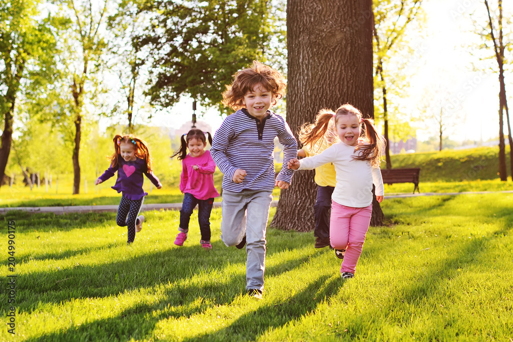 Fototapety, obrazy: many young children smiling running along the grass in the park. Childhood, Children's Day, vacation, vacation, adventure, friendship.