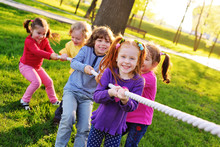A Group Of Small Preschool Children Play A Tug Of War In The Park. Outdoor Games, Childhood, Friendship, Leadership, Children's Day.