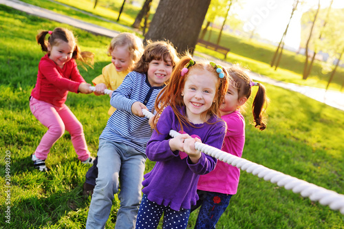 Fotografía  a group of small preschool children play a tug of war in the park