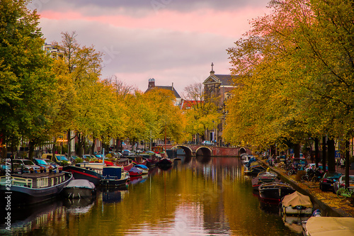 Photo  Beautiful sunset evening in Amsterdam over canals with boats and trees