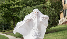 A Child In A Ghost Costume Made Out Of A Bedsheet Running Down The Sidewalk.