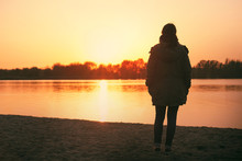 A Young Caucasian Woman Standing Near The Shoreline Of A Lake Watching The Sunset By Herself Thinking And Contemplating