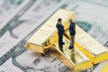 Deal Or Negotiation In Investment, Gold, Wealth Management Concept, Miniature People Rich Businessman Shaking Hand On Gold Bar, Bullion Or Ingot Stack On US Dollar Banknote Money