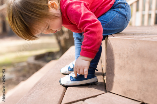 Fotobehang Stof Happy toddler boy tying his sneakers outside