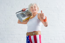 Cheerful Senior Sportswoman Holding Tape Recorder And Showing Thumb Up