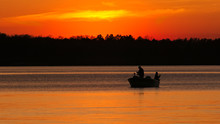Silhouette Of Father And Son Fishing On Lake Irving At Sunset In Bemidji, Minnesota.