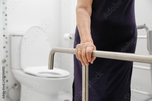 Poster  Elderly woman holding on handrail in toilet.