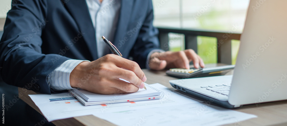 Fototapeta Businessman analysis maketing plan, Accountant calculate financial report, computer with graph chart.  Business, Finance and Accounting concepts
