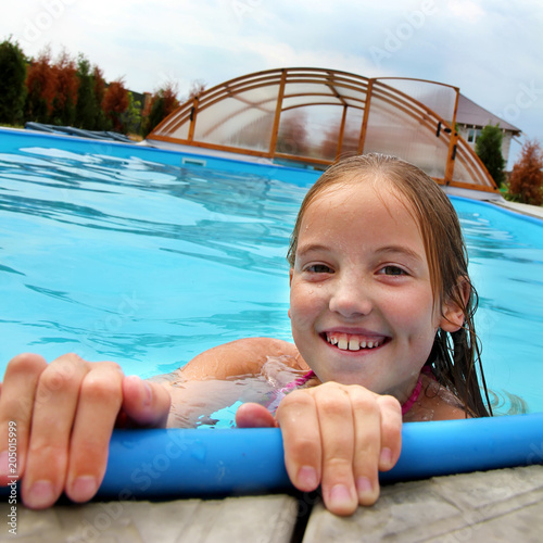 Valokuva  head of a smiling little girl in the pool